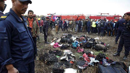 Authorities survey the luggage of passengers aboard a doomed flight landing in Kathmandu. (AAP)