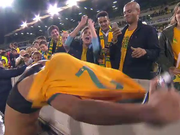 Socceroos defender James Meredith takes off his jersey while a young female fan screams in joy hoping to get it. (Supplied)