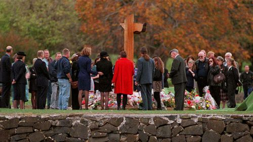 Families and friends gather around the memorial at Port Arthur a year after the tragedy in 1997.