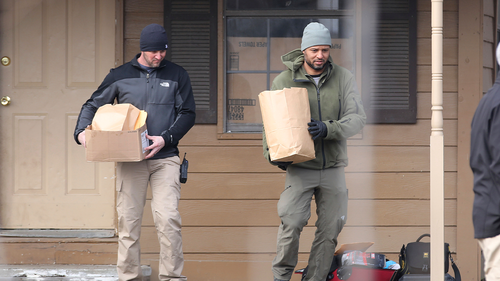 Investigators remove items from the scene of a suspected mass homicide where at least five children were slain Tuesday, Feb. 2, 2021 in Muskogee, Oklahoma.