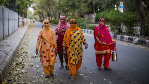 Indian women carry containers to buy milk as they walk on a deserted road , amid a nationwide lockdown.