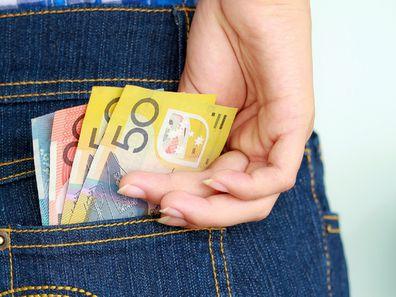 Woman placing Australian money in her back pocket.