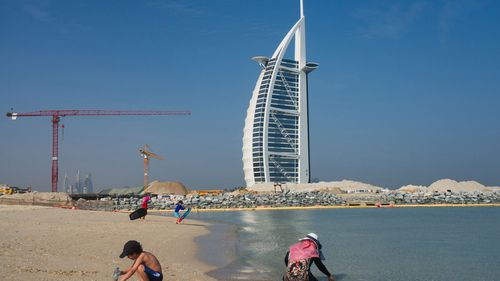 Families play on a public beach with the Burj al-Arab hotel behind them in Dubai, United Arab Emirates, Friday, May 29, 2020