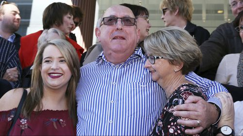 Mr Creigh embraces family members outside Newcastle Local Court. (AAP)