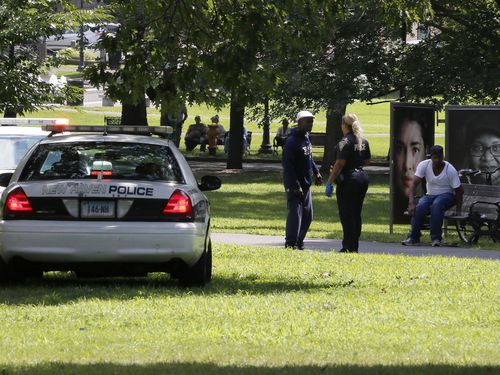 A police officer speaks to a man walking on New Haven Green, Wednesday, Aug. 15, 2018, in New Haven, Conn. A city official said more than a dozen people fell ill from suspected drug overdoses on the green and were taken to local hospitals.