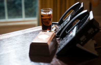A glass of iced soda is seen on the Resolute Desk as President Donald Trump speaks to media