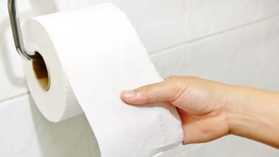 Woman hand holding the roll of toilet paper