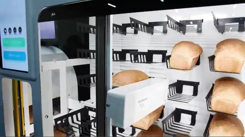 A bread vending machine bakes and delivers hot, fresh loaves.