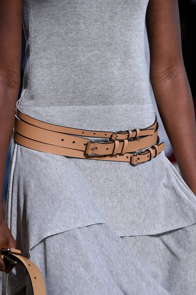 Belts in neutral leather, layered for a modern twist.