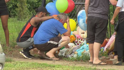 Mr Shorey is comforted at the crash scene where his two sons were killed.