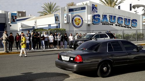 Students stand outside of Saugus High School after a mass shooting.