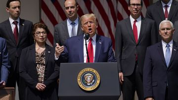 President Donald Trump speaks during a news conference in the Rose Garden of the White House, Friday, June 5, 2020, in Washington. Front row from left, Small Business Administration administrator Jovita Carranza, Trump, and Vice President Mike Pence. Back row from left, member of Council of Economic Advisers Tyler Goodspeed, Labor Secretary Eugene Scalia, Treasury Secretary Steven Mnuchin, and Chairman of the Council of Economic Advisers Tomas Philipson