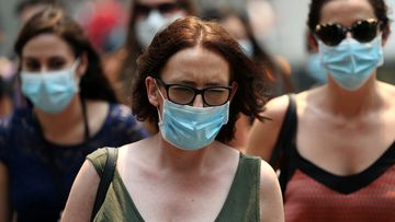 People wear face masks to protect from smoke haze as they cross a busy city street in Sydney, Australia