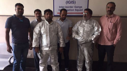 """Dressed in """"space suits"""", the two men were arrested by police for conning a businessman."""