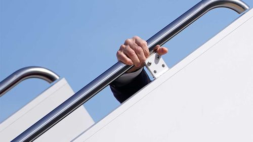 Joe Biden clings to the railing after slipping on the steps of Air Force One.
