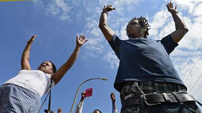 Demonstrators hold up their hands in protest next to a cordoned-off area where unarmed youth Michael Brown was shot dead by police. (AP)