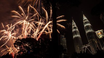 Malaysia's iconic Petronas Towers were almost out-shone by the golden glow of pyrotechnics. (AAP)