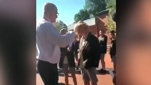 Mr Brown was filmed trimming a student's hair on school photo day. (The Age)