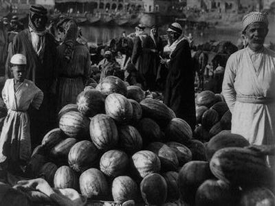 In this photo taken in 1932, men hang out in the fruit market with a pile of watermelons ready for buyers.<br /> (American Colony Photo Department)