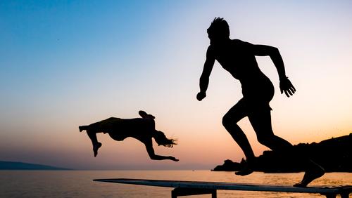 People jump into the lake Geneva on a hot summer day at sunset in Saint Saphorin, Switzerland.