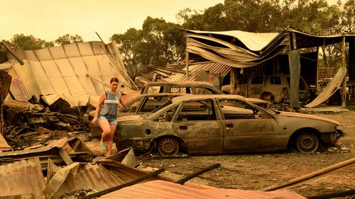 A woman picks through the burnt-out remains of a property in Tingha.