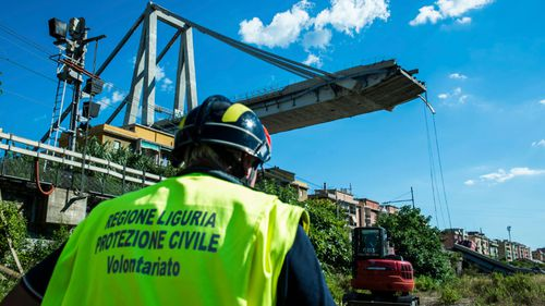 A worker inspects the the area around the collapsed Morandi highway bridge, in Genoa, northern Italy.
