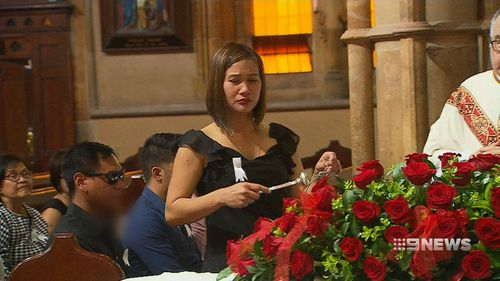 Ms Nilsson sprinkled holy water on her alleged victim's coffin. (9NEWS)