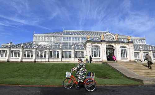 A woman cycles past the newly restored Victorian Temperate House in Kew Gardens. (AAP)