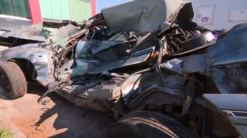 """The owner of the crumpled Holden wants it to remain on the road as a reminder for drivers to """"slow down"""". (9NEWS)"""