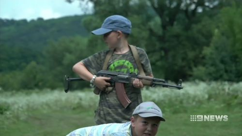 Children are taught to handle and use rifles.