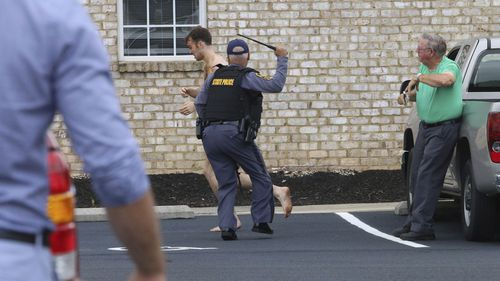 A policeman strikes Matthew Bernard with a baton after he charged at a church caretaker.