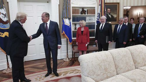 Donald Trump meeting with Sergey Lavrov, with a woman falsely purported to be Mariia Butina in the background. (TASS)