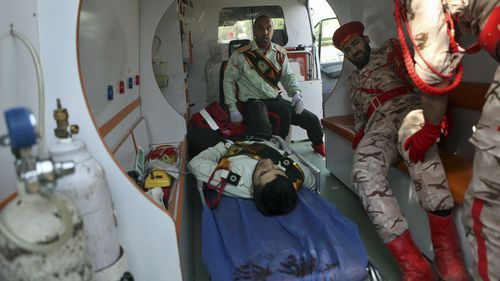 Wounded military personnel are carried into an ambulance after a shooting during a military parade marking the 38th anniversary of Iraq's 1980 invasion of Iran, in the southwestern city of Ahvaz, Iran. (AP)