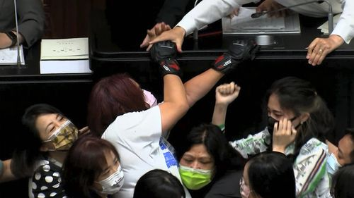 Opposition Nationalist party lawmaker Chen Yu-jen, in white shirt, is grabbed by ruling Democratic Progressive Party lawmakers as she tries to climb onto the podium during a parliament session in Taipei.
