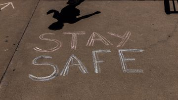 A stay safe sign is chalked on the pavement in Broken Hill.