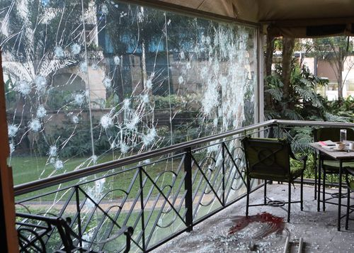 The bullet-riddled window of a cafe in the complex where dead bodies are clearly visible.