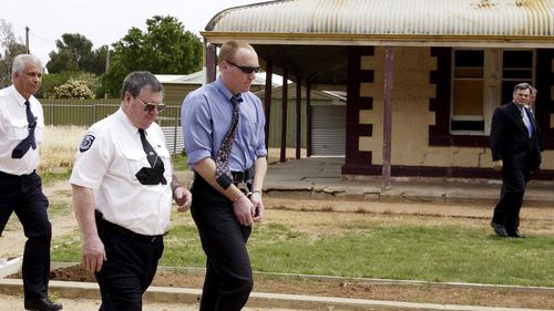 File photo from 2002 of accused murderer Robert Joe Wagner is escorted handcuffed by a court sherriff outside the house 25 Railway Tce in Snowtown.