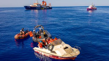 "The pink rescue boat ""Louise Michel"" (back R) is pictured off the Libyan coast on August 22, 2020. The boat, helped to rescue 89 people on Thursday, according to a spokesperson for the vessel."
