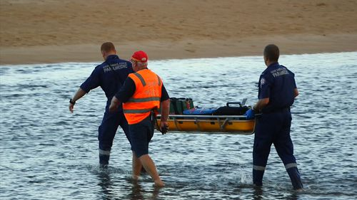 Emergency services carry a stretcher filled with medical gear through the shallows.