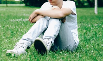 Teenage boy sitting at the park