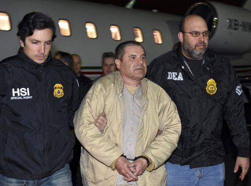 "In this Jan. 19, 2017 file photo provided U.S. law enforcement, authorities escort Mexican drug lord Joaquin ""El Chapo"" Guzman, center, from a plane in Ronkonkoma, N.Y. A judge has postponed the New York trial of Guzman until November 2018. U.S. District Judge Brian Cogan in Brooklyn on Monday, July 16, said jury selection can start Nov. 5. Guzman's lawyer says his client is ""highly disappointed"" that the judge did not delay the trial five months. (U.S. law enforcement via AP, File)"