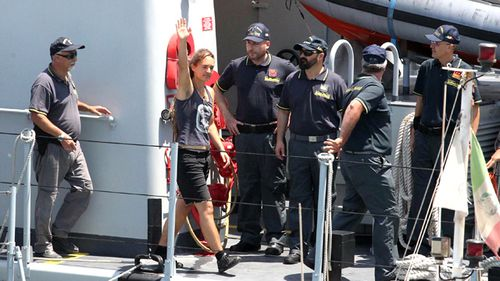 Sea-Watch 3 captain Carola Rackete, from Germany, waves as she arrives in the Sicilian port of Porto Empedocle, escorted by Italian finance police on Monday, July 1.
