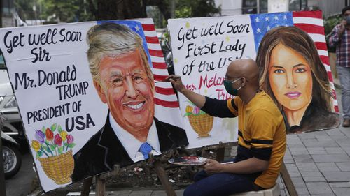 An artist from Gurukul art school paints a poster carrying a message for US President Donald Trump and first lady Melania in Mumbai, India.