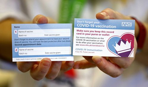 A model holds a card which will be given to patients following their vaccination for COVID-19 at Croydon University Hospital in south London on December 5, 2020, where the first batch of COVID-19 vaccinations has been delivered to the area.