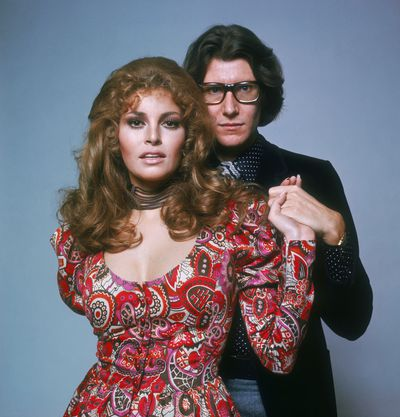 Yves Saint Laurent (here with Raquel Welch in 1975) has become the subject of duelling biopics in recent years.