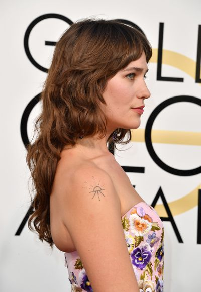 <p>Lola Kirke's gown was sprinkled with flowers in all shades making her pretty as a walk in the country. She added a touch of rock chick chic with a cool shoulder tattoo.</p> <p>Image: Getty.</p>