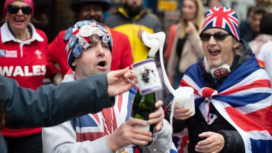 Royal fans celebrate in the streets of Windsor popping bottles of champagne upon the announcement of baby Sussex's birth
