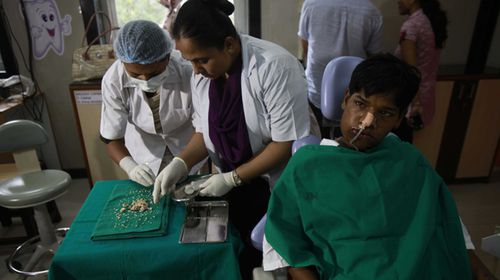 Ashik Gavai sits on a patient chair after his extractions as the dentists count his teeth. (Getty)