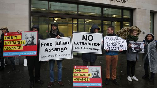 Supporters of WikiLeaks founder Julian Assange protest in front of Westminster Magistrates Court in London, Friday, Dec. 20, 2019. Assange is expected to appear in person before Westminster Magistrates in a private hearing related to a Spanish criminal case about alleged surveillance at the Ecuador embassy.