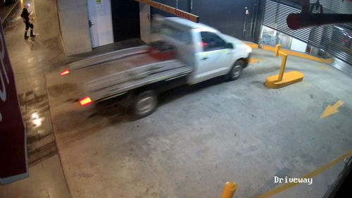 The thief drives a stolen ute under the closing gates of a Sydney apartment block.